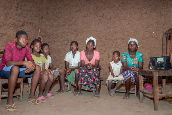 Camila with her 5 siblings and mother sitting in their mud house.