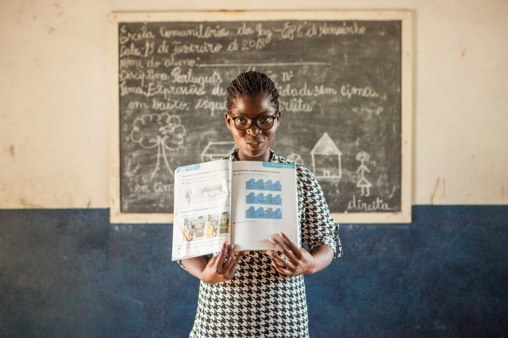 A teacher from Peace school in Mozambique standing with an open book in front of the classroom