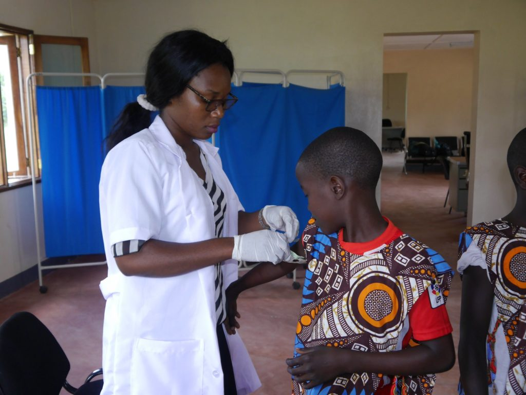 A boy from Peace school in Mozambique receiving a vaccination
