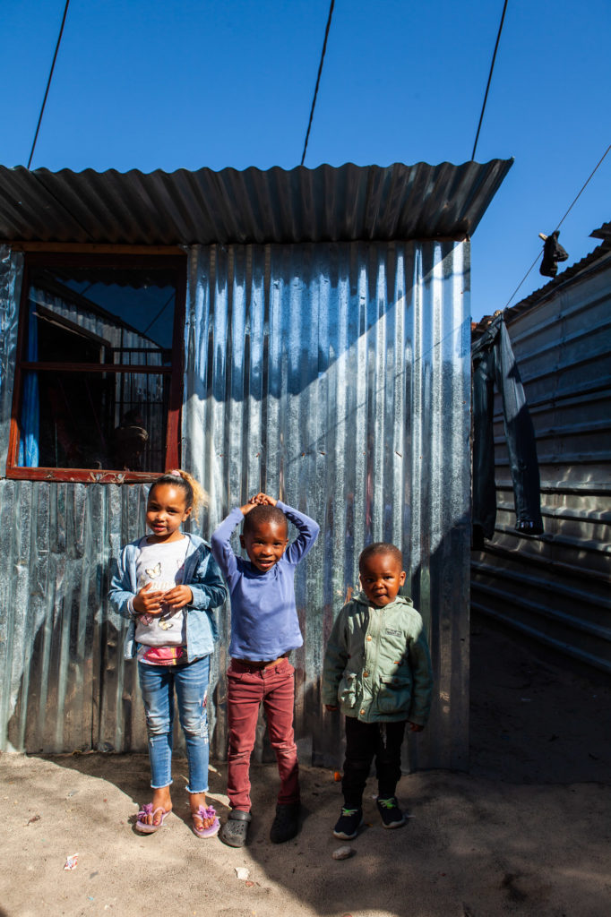 Isabella, her brother and cousin standing next to their new house