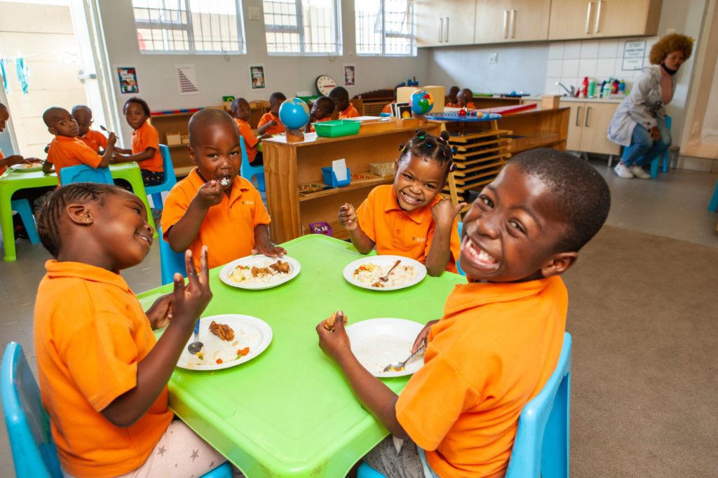 Ndinawe smiling while sitting at the table and having lunch with his friends